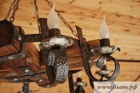 Деревянная люстра с элементами ковки привлекает внимание своей средневековой естественностью, изысканностью и теплотой