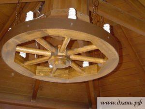 Яркий вариант осветительного прибора – деревянная люстра в виде колеса, включающая элементы старины