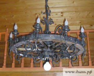 Люстра в форме колеса из дерева и кованого металла с лампами в виде свечек.