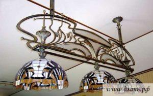 Изящное сочетание кованых элементов с цветным стеклом сделает этот кованый потолочный светильник отличным дополнением для интерьера в современном стиле
